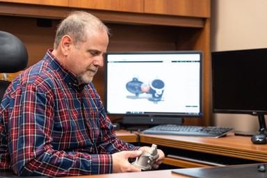 Robert Ginberg inspecting a 3D printed part at his desk