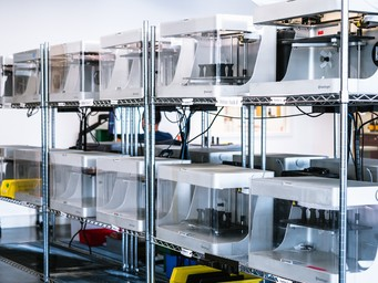 Rack of Markforged 3D printers producing parts